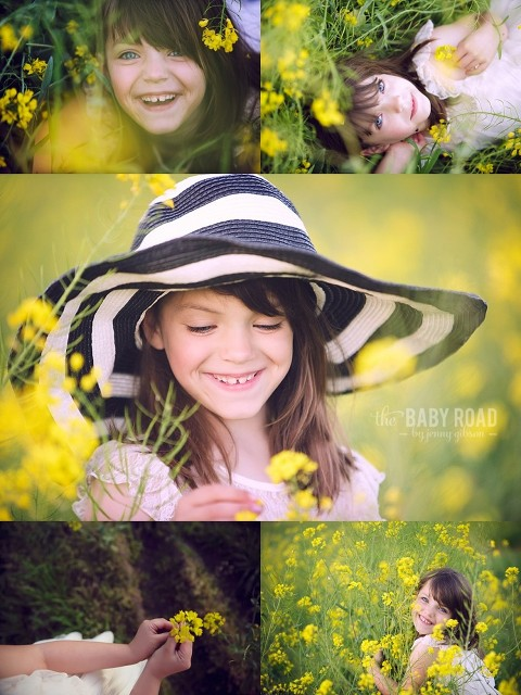 blue eyed little girl laying in yellow flowers, holding flowers and wearing a striped hat